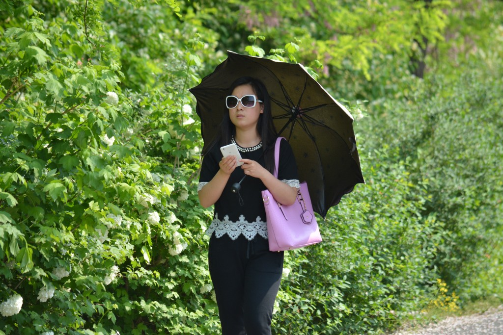 A walk in the park doesn't always mean hiking shoes and cargo shorts.  And the Chinese don't go to the park for sun.  Parasols are a common accessory.  To the Chinese sun and skin are not are not a healthy combination.