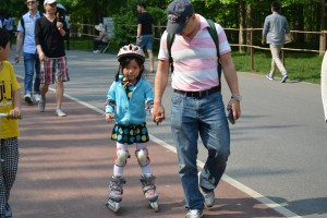 Roller blades are an uncommon sight in China but this dad's hat said Harvard, so perhaps he brought the interest back with him and is transferring it to his daughter.